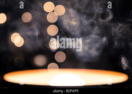 Abstract photo of a pendant lamp turned by 180 degrees, cigarette smoke in the foreground, Bokeh, string of lights, dark background - Stock Photo