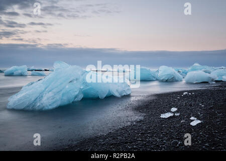 Blue shimmering blocks of ice in blurred water on black beach at Jökulsárlón (Diamond Beach), Iceland, morning mood - Stock Photo
