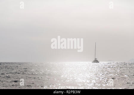 Monochrome, gray, minimalist image of a single sailing boat on the open sea, glistening brightly in the sun - Stock Photo