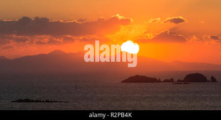 Glowing sun above the sea with offshore island and clouds, setting behind a hill, above the sea - Stock Photo