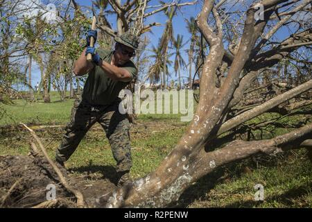Sgt. Juan Acosta, a food service specialist with Combat Logistics Battalion 31, chops a fallen tree at the veteran's memorial during U.S. Defense Support of Civil Authorities relief efforts on Tinian, Commonwealth of the Northern Mariana Islands, Nov. 4, 2018. Acosta, a native of Los Angeles, graduated from Huntington Park High School in May 2012 before enlisting in October the same year. Businesses, government buildings, homes and schools were heavily damaged by Super Typhoon Yutu, which made a direct hit with devastating effect on Tinian Oct. 25 packing 170 MPH winds – it is the second stron - Stock Photo