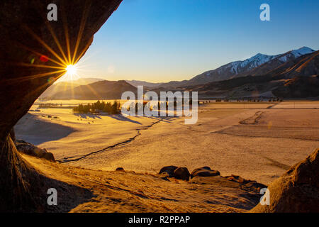 The sun rises over the mountain range and casts a golden glow over the farmland on a frosty morning Stock Photo