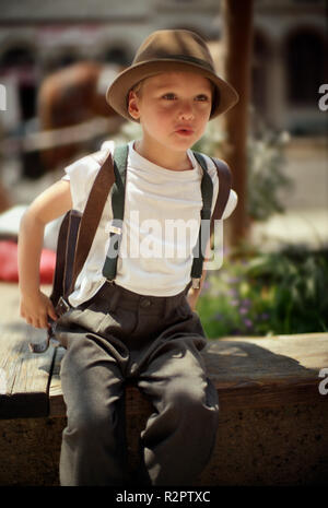 Boy in hat and suspenders - Stock Photo