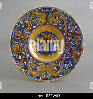 Plate with border of foliate scrollwork with dolphin heads and cornucopias; in the center, shield of arms of Vigerio of Savona. Dated: 1524. Dimensions: overall (diameter): 36.5 cm (14 3/8 in.). Medium: tin-glazed earthenware (maiolica). Museum: National Gallery of Art, Washington DC. Author: Workshop of Maestro Giorgio Andreoli of Gubbio. - Stock Photo