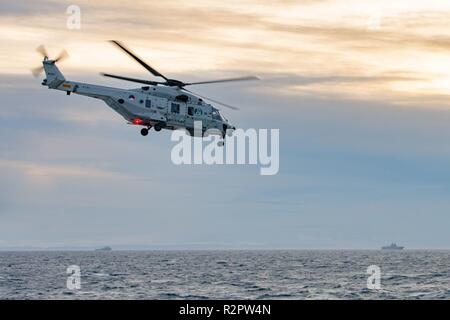NORWAY, Oct. 31 2018. GEN. SNMG2 VESSELS ESCORT AMPHIBIOUS TASK GROUP.  A Royal Netherlands Navy NH-90 takes off from HNLMS De Ruyter duirng NATO exercise Trident Juncture on October 31, 2018.    Trident Juncture 18 is designed to ensure that NATO forces are trained, able to operate together and ready to respond to any threat from any direction. Trident Juncture 18 takes place in Norway and the surrounding areas of the North Atlantic and the Baltic Sea, including Iceland and the airspace of Finland and Sweden.     With around 50,000 participants from 31 nations Trident Juncture 2018 is one of  - Stock Photo