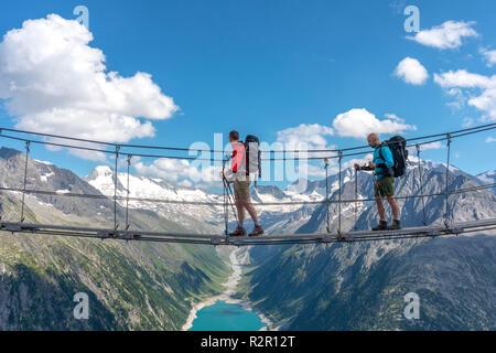 Two hikers on the tibetan bridge near Olperer hut with Schlegeis Stausee on the background, Zillertal Alps, Tyrol, Schwaz district, Austria. - Stock Photo