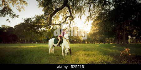 Mother hugging her daughter while she sits upon her horse. - Stock Photo