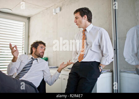 Young adult business man talking with a male colleague while leaning back on his chair in an office. - Stock Photo