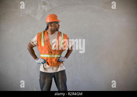 Dirty mid-adult construction worker standing with his hands on his hips while wearing a helmet and hi-visibility vest. - Stock Photo