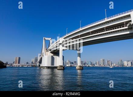Tokyo, Japan - Jan 4, 2016. Rainbow Bridge and cityscape in Tokyo, Japan. The bridge was built by Kawasaki Heavy Industries, with construction startin - Stock Photo