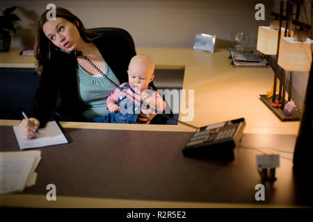 Mid-adult business woman on the phone while holding a baby in an office. - Stock Photo