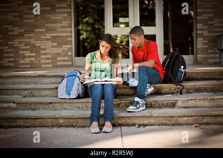 Teenage boy and girl looking at a book sitting on steps outside a school. - Stock Photo