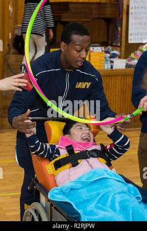 KOJE-DO, Republic of Korea (Nov. 03, 2018) Intelligence Specialist 3rd Class Langston Greer, assigned to Commander, U.S. Naval Forces Korea, participates in a community relations event with a resident of the Aikwangwon Home and School for the Mentally and Physically Disabled in Koje-do. The U.S. Navy and Aikwangwon community outreach program spans more than 60 years and began when U.S. Navy doctors and nurses assigned to the U.S. Navy base in Chinhae volunteered at the home during the Korean War. - Stock Photo