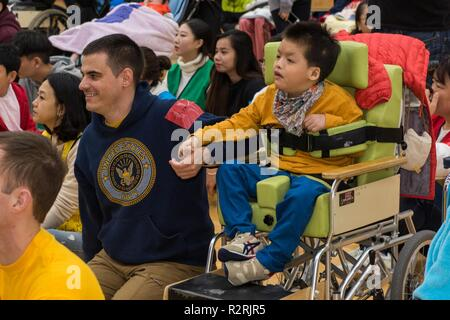 KOJE-DO, Republic of Korea (Nov. 03, 2018) Operations Specialist 2nd Class Tyler Whitney, assigned to Commander, U.S. Naval Forces Korea, participates in a community relations event with residents of the Aikwangwon Home and School for the Mentally and Physically Disabled in Koje-do. The U.S. Navy and Aikwangwon community outreach program spans more than 60 years and began when U.S. Navy doctors and nurses assigned to the U.S. Navy base in Chinhae volunteered at the home during the Korean War. - Stock Photo