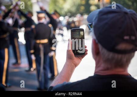 A member of the audience films the U.S. Army Drill Team performing after the 4th Annual Philadelphia Veterans Day Parade in Philadelphia, Pennsylvania, November 4, 2018. - Stock Photo