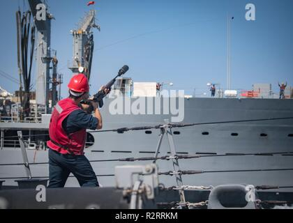 ARABIAN GULF (Nov. 5, 2018) Fire Controlman 2nd Class Alexis Suarez fires a shot line over to the fleet replenishment oiler USNS Kanawah (T-AO 196) from the Arleigh Burke-class guided-missile destroyer USS Jason Dunham (DDG 109) during a replenishment-at-sea. Jason Dunham is deployed to the U.S. 5th Fleet area of operations in support of naval operations to ensure maritime stability and security in the Central Region, connecting the Mediterranean and the Pacific through the western Indian Ocean and three strategic choke points. - Stock Photo
