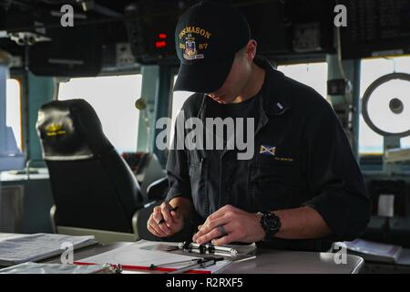 ATLANTIC OCEAN (Nov. 4. 2018) Lt. j.g. Scott Monter uses a maneuvering board to log contacts' true course and true speed on the bridge aboard the guided-missile destroyer USS Mason (DDG 87). USS Abraham Lincoln (CVN 72) Carrier Strike Group (CSG) cruiser-destroyer (CRUDES) units are completing the first east coast CRUDES Surface Warfare Advanced Tactical Training (SWATT) exercise. SWATT is led by the Naval Surface and Mine Warfighting Development Center (SMWDC) and is designed to increase warfighting proficiency, lethality, and interoperability of participating units. - Stock Photo