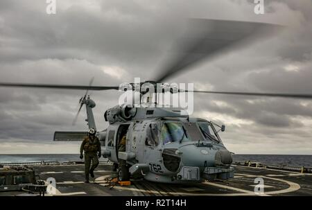 ATLANTIC OCEAN (Nov. 8, 2018) Lt. Chris Thompson prepares to take off in an MH-60R Seahawk helicopter from the Grandmasters of Maritime Strike Squadron (HSM) 46 during a crew swap aboard the Arleigh Burke-class guided-missile destroyer USS Nitze (DDG 94). USS Abraham Lincoln (CVN 72) Carrier Strike Group (CSG) cruiser-destroyer (CRUDES) units are completing first East Coast CRUDES Surface Warfare Advanced Tactical Training (SWATT) exercise. SWATT is led by the Naval Surface and Mine Warfighting Development Center (SMWDC) and is designed to increase warfighting proficiency, lethality, and inter - Stock Photo