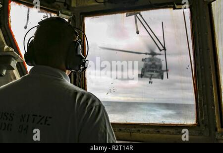 ATLANTIC OCEAN (Nov. 8, 2018) Lt. j. g. Nick Holcomb mans the control tower aboard the Arleigh Burke-class guided-missile destroyer USS Nitze (DDG 94) as an MH-60R Seahawk helicopter from the Grandmasters of Maritime Strike Squadron (HSM) 46 takes flight. USS Abraham Lincoln (CVN 72) Carrier Strike Group (CSG) cruiser-destroyer (CRUDES) units are completing the first East Coast CRUDES Surface Warfare Advanced Tactical Training (SWATT) exercise. SWATT is led by the Naval Surface and Mine Warfighting Development Center (SMWDC) and is designed to increase warfighting proficiency, lethality, and i - Stock Photo