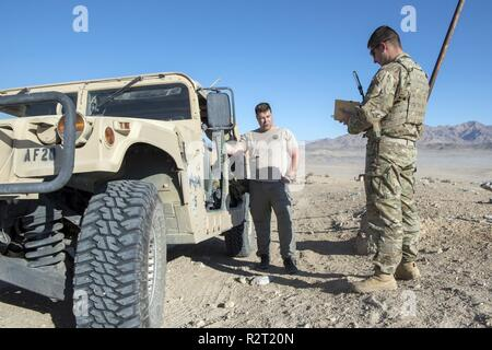 """Technical Sgt. Eric Maertens, Survival, Evasion, Resistance, and Escape(SERE) specialist and  Staff Sgt. Michael Pincheira, 12CTS Field Instructor at Ft. Irwin National Training Center, California, discuss the pilot extraction exercise that had just taken place.  Pilots Capt. Phil """"Upper"""" Butler and Capt. John """"Harden"""" Toliuszis simulated downed pilots and had to survive until rescue forces could retrieve them, while evading opposing forces.  This training is part of a larger exercise based out of Nellis AFB, Nevada, where approximately 200 members of the Colorado Air National Guard and over  - Stock Photo"""