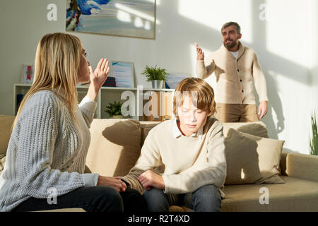 Mother protecting son and yelling at husband - Stock Photo
