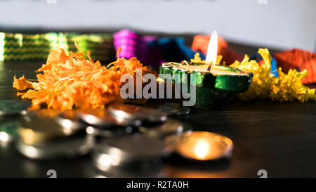 Diya lit decorated with flowers and coins for celebrating diwali and dhanteras - Stock Photo