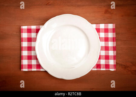 An overhead photo of a white plate on a gingham cloth on a dark rustic wooden background with copy space - Stock Photo