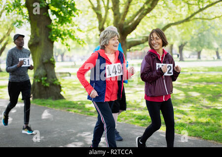 Active senior women friends power walking sports race in park - Stock Photo