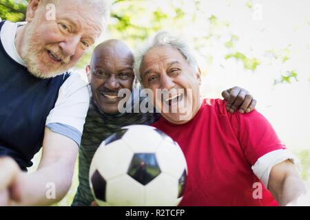 Portrait active senior men friends playing soccer - Stock Photo
