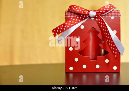 Red box with a candle inside and white and red ribbon for Christmas decoration. Copy space, bokeh