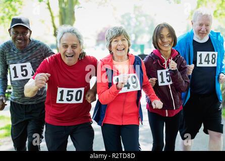 Portrait enthusiastic active senior friends running sports race - Stock Photo