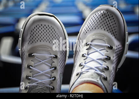 Close up top view of pair of ladies classic white sneakers with grey trim. Modern lifestyle footwear for men and women, with sporting venue background - Stock Photo