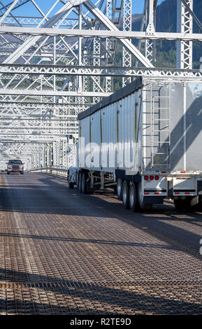 Classic American bonnet big rig burgundy semi truck with shiny refrigerator semi trailer with reefer unit on it driving trough truss Bridge of God in  - Stock Photo