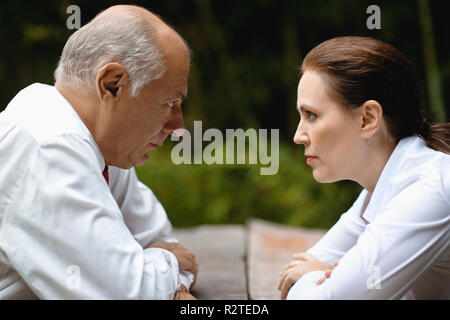 Businessman and woman facing off. - Stock Photo