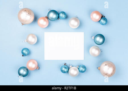 Frame of Christmas balls with blank card mockup on blue background. Holiday background, top view. - Stock Photo