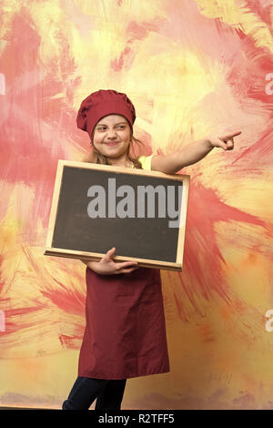 Small girl cook in hat with blackboard or chef child in apron presenting product on colorful background, copy space - Stock Photo