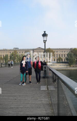 Peoples on Pont des Arts footbridge on the Seine River and People walking across a pedestrian bridge over the River Seine facing the Louvre museum - Stock Photo