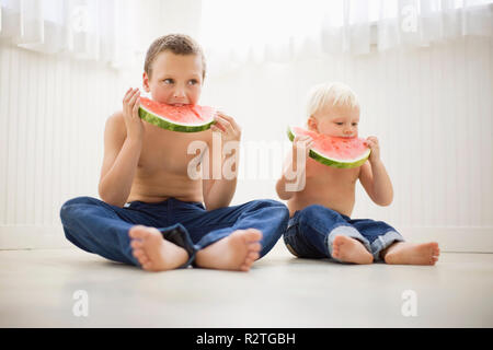 Two brothers dressed identically and eating watermelon - Stock Photo