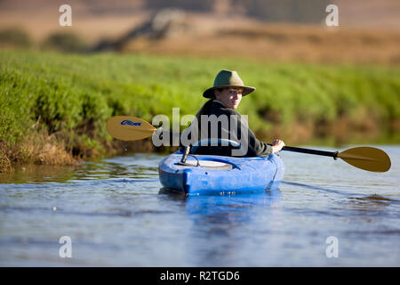 Portrait of a young woman looking over her shoulder while sitting in a blue kayak on a lake. - Stock Photo