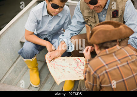 Father looking at a treasure map with his two sons while dressed as pirates and sitting in a rowboat. - Stock Photo
