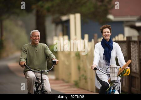 Mature man and a young woman having fun while riding bicycles through a suburban neighborhood. - Stock Photo