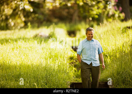 Mature man smiling as he walks in a park - Stock Photo