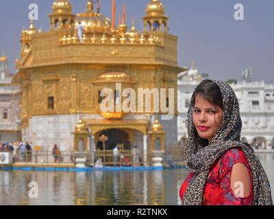 Young Indian beauty poses in front of the Golden Temple. - Stock Photo