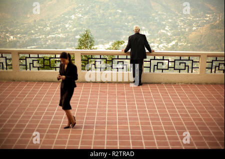 Businessman looks out on a city valley from a balcony as a female colleague walks away across the paved floor. - Stock Photo