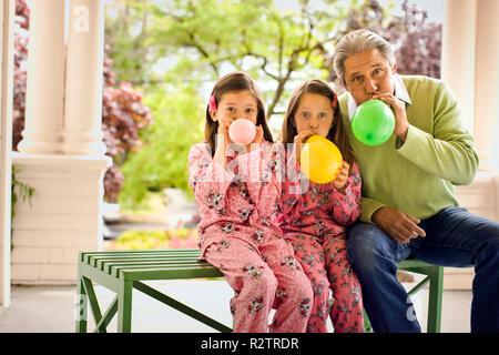 Two young girls in matching pajamas sit with a mature man on a bench on a porch and blow up a balloon each as they pose for a portrait. - Stock Photo