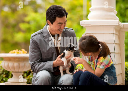 Portrait of father and daughter playing with a puppy. - Stock Photo