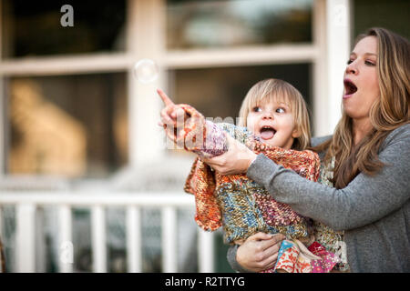 Mother holding toddler daughter as she reaches out to pop bubble. - Stock Photo