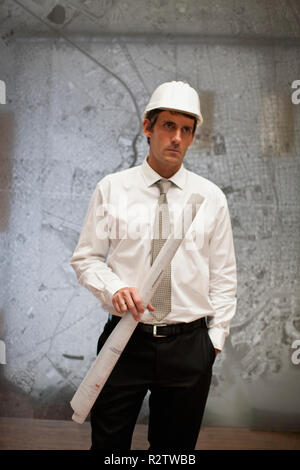 Businessman in a hardhat and carrying a roll of building plans stands before metal wall map and poses for a portrait. - Stock Photo