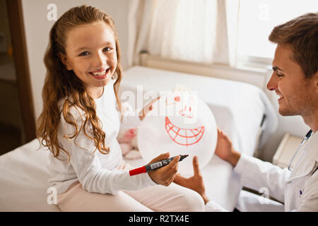 Male doctor sitting with his young female patient, drawing face on balloon made from rubber glove. - Stock Photo
