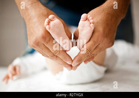 Close up of man's hands holding his baby's feet and creating heart shape. - Stock Photo
